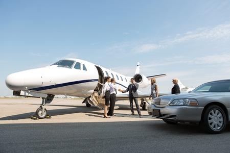 millonario: Los corporativos saludo azafata y piloto cerca de jet privado y limusina en la terminal de aeropuerto Foto de archivo