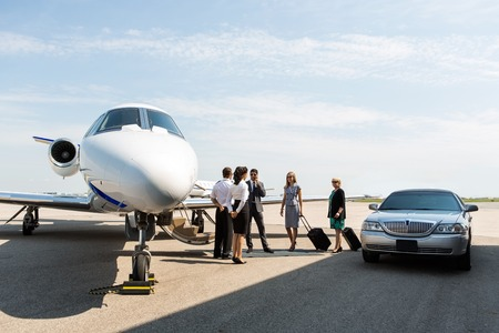 Gente di affari con pilota e airhostess piedi vicino jet privato e limousine al terminal