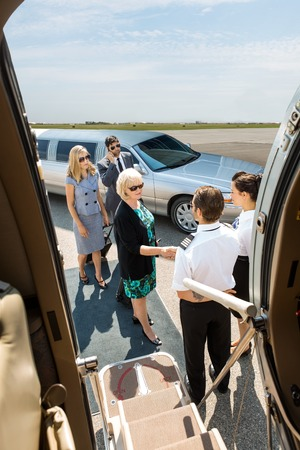 Airhostess and pilot greeting corporate people before boarding private jet photo