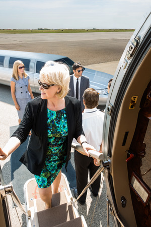 Mature businesswoman boarding private jet with colleagues and pilot at airport terminal photo