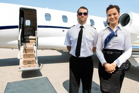 Portrait d'hôtesse de l'air confiant et pilote debout contre jet privé