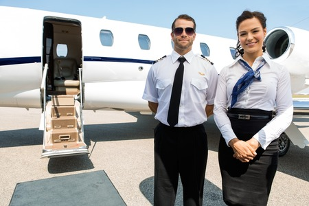 private airplane: Portrait of confident stewardess and pilot standing against private jet