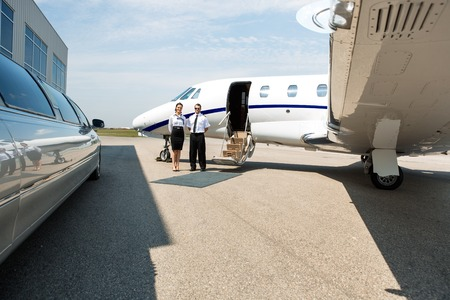 Stewardess and pilot standing neat limousine and private jet at airport terminal photo