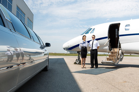 stewardess: Flight attendant and pilot standing neat limousine and private jet at airport terminal