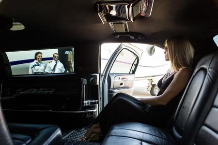 mujer elegante: Mujer elegante en limusina con azafata y piloto de cerca jet privado en el terminal