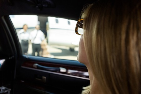 Closeup of elegant woman in limousine at airport terminal photo