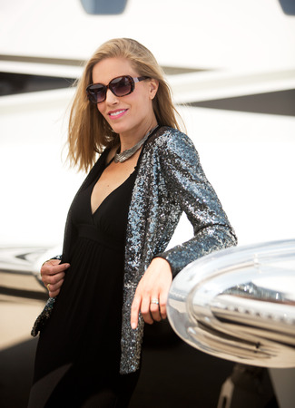 Young diva leaning on private jet wing photo