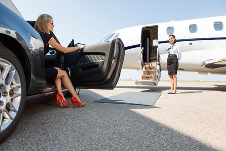mujer adinerada saliendo del automóvil estacionado frente a un avión privado y azafata Foto de archivo