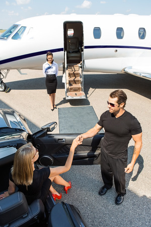 High angle view of bodyguard assisting elegant woman stepping out of car at airport terminal photo
