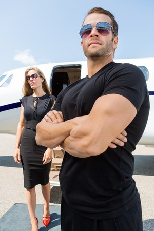 private security: Bodyguard with arms crossed standing against woman and private jet Stock Photo