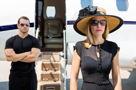 Beautiful woman wearing sunhat with bodyguard and private jet in background photo