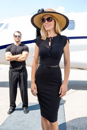body guard: Happy woman in elegant dress with bodyguard and private jet in background Stock Photo