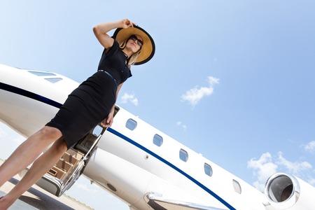 하늘에 개인 제트기의 앞에 우아한 드레스 서에서 여자의 낮은 각도보기 스톡 콘텐츠