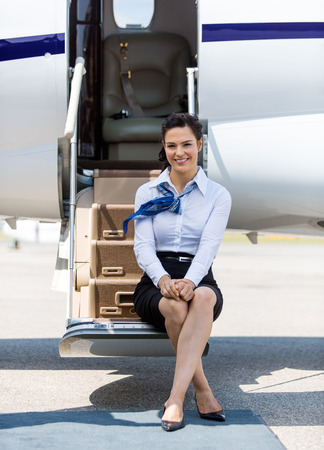 an attendant: Full length portrait of beautiful air hostess sitting on ladder of private jet Stock Photo