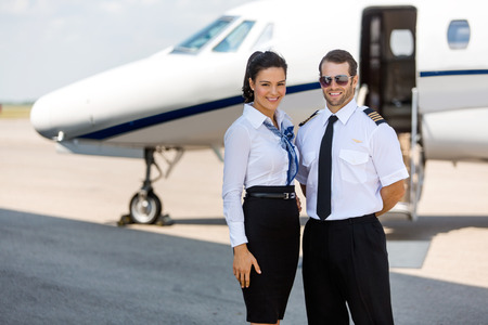 airhostess: Portrait of happy airhostess and pilot standing against private jet at terminal Stock Photo