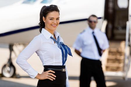 air hostess: Portrait d'hôtesse de l'air attrayant avec pilote et jet privé en arrière-plan à la borne Banque d'images