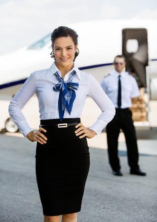 air hostess: Portrait d'hôtesse de l'air à l'aise avec les mains sur la hanche contre pilote et jet privé au terminal de l'aéroport Banque d'images