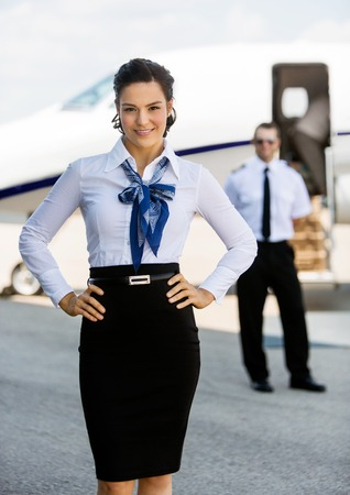 airhostess: Portrait of confident airhostess with hands on hip against pilot and private jet at airport terminal