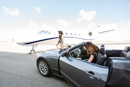 Portrait of woman disembarking car with private jet in background at terminal