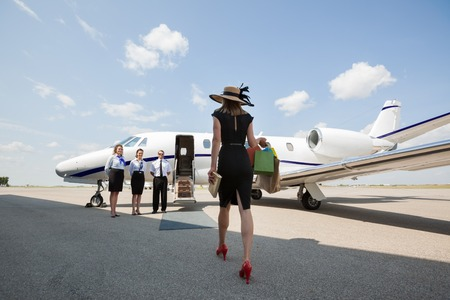 Rear view of woman walking towards private jet while pilot and stewardesses standing at airport terminal photo
