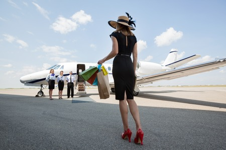 Full length rear view of woman carrying shopping bags while walking towards private jet at airport terminal photo