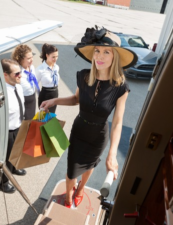 Full length portrait of confident rich woman carrying shopping bags while boarding private jet with pilot and airhostess standing by at airport terminal photo