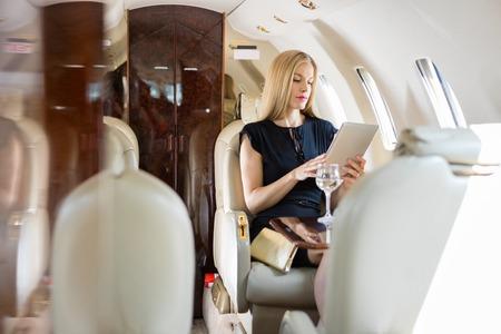 개인 제트기에서 태블릿 컴퓨터를 사용하여 리치 중반 성인 여자
