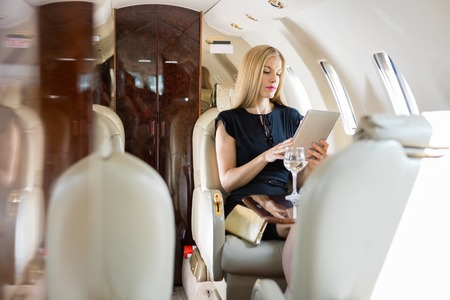 Rich mid adult woman using tablet computer in private jet photo