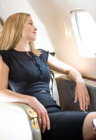 rijke vrouw: Aantrekkelijke rijke vrouw kijkt door raam in prive-jet Stockfoto