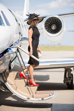 disembarking: Side view of wealthy woman disembarking private jet at airport terminal Stock Photo