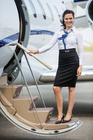 airline pilot: Full length portrait of young stewardess standing on ladder of private jet
