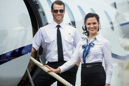 airline pilot: Portrait of happy confident airhostess and pilot standing on private jets ladder