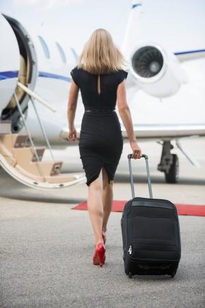 空港ターミナルでプライベート ジェットに向かって歩いて荷物を持つ裕福な女性の完全な長さ背面図