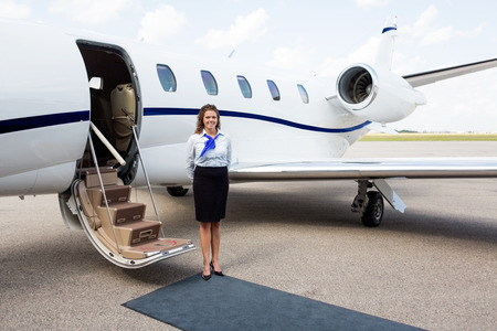 Full length portrait of airhostess standing by private jet at airport terminal photo