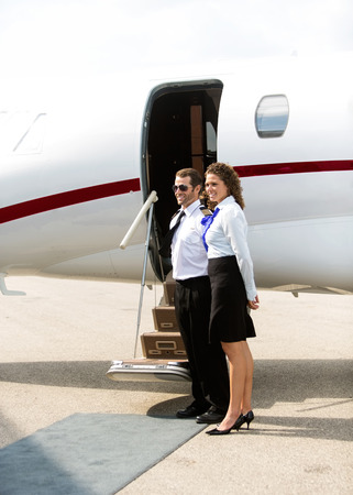 Full length of stewardess and pilot standing against private jet photo