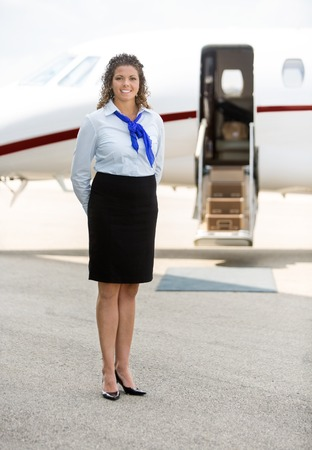 Full length of beautiful stewardess standing against private jet at terminal photo