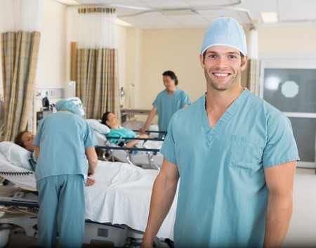 operative: Portrait of happy male nurse with colleagues in surgery ward at hospital Stock Photo