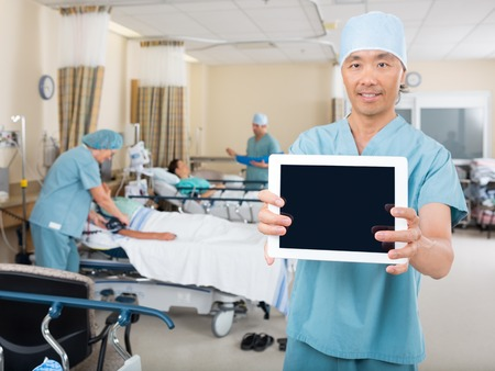 Portrait of male nurse showing digital tablet in hospital ward Stock Photo - 25762173