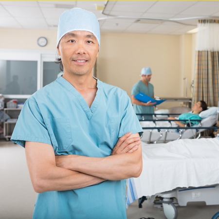 pacu: Portrait of confident mid adult male nurse standing in hospital ward Stock Photo