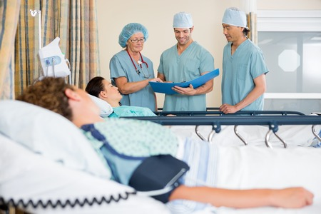 Team of nurses examining patient's report in surgical recovery unit Stock Photo - 25762178