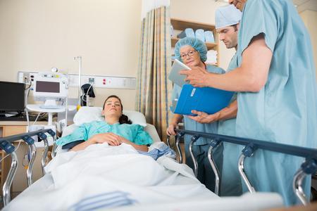 病棟のベッドで女性患者のレポートを議論する多民族の看護師