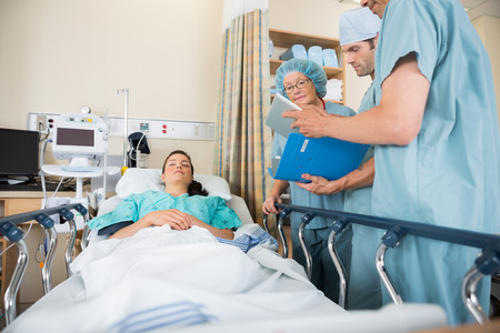 Multiethnic nurses discussing female patient's report by bed in hospital ward Stock Photo - 25762179