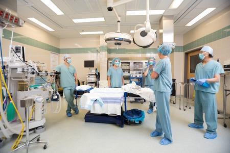 equipos medicos: Equipo médico que tiene una discusión en la sala de operación