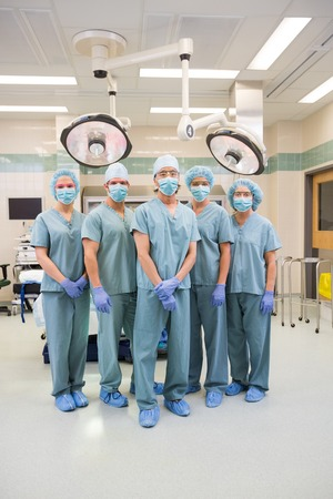 Full length portrait of surgical team in scrubs standing inside operation room photo