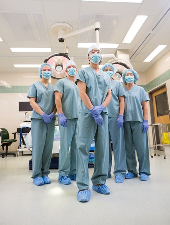 Low angle view of multiethnic medical team standing in operation room photo