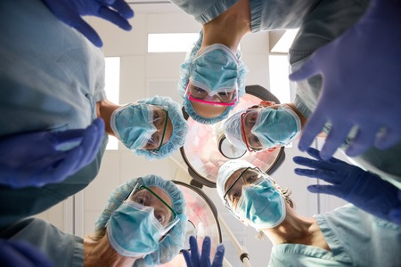 Directly below portrait of multiethnic medical team with masks and scrubs in operation room photo