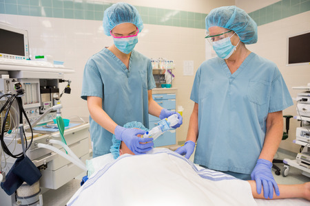 Female nurses putting oxygen mask on patient in operation room photo