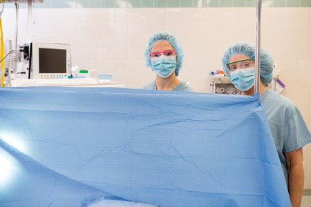 Anesthesiologist standing behind curtain in operating theater photo