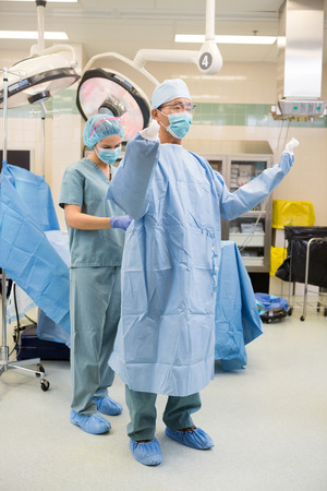 operating theater: Full length of scrib nurse assisting surgeon to put on gown in operating theater