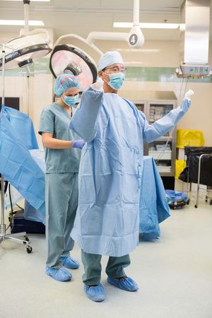 enfermera con cofia: Longitud total de la enfermera scrib asistir cirujano a poner en el vestido en el teatro de operaciones Foto de archivo